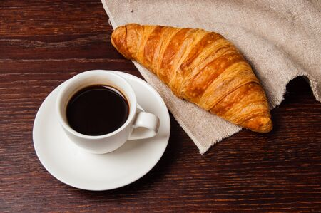 Tasty rustic breakfast. Croissant and coffee in a white cup, top view, flat lay Standard-Bild - 138720851