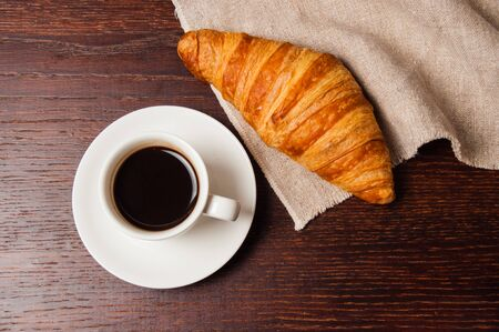 Tasty rustic breakfast. Croissant and coffee in a white cup, top view, flat lay Standard-Bild - 138720665