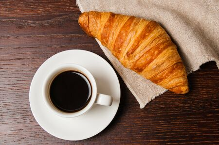 Tasty rustic breakfast. Croissant and coffee in a white cup, top view, flat lay Standard-Bild - 138720957