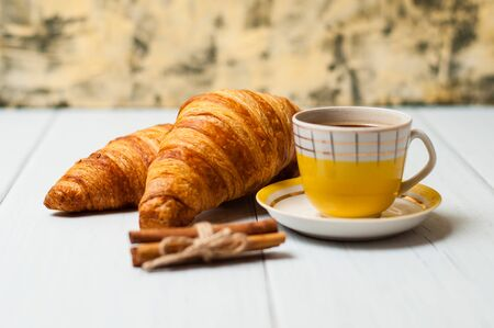 Espresso coffee in a vintage yellow cup, croissants and cinnamon on a light background, breakfast concept Standard-Bild - 138721007
