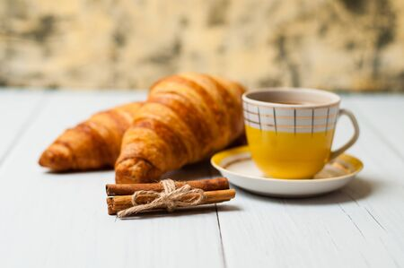 Espresso coffee in a vintage yellow cup, croissants and cinnamon on a light background, breakfast concept Standard-Bild - 138720743