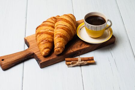 Espresso in vintage yellow cup, croissants and cinnamon on a wooden board, on a light background, concept of lunch Standard-Bild - 138720576