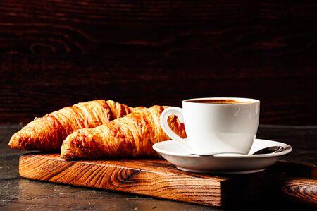 Concept of delicious breakfast, croissants and espresso on a dark wooden board. Standard-Bild - 138720864