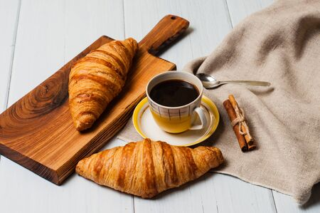 Coffee in a vintage yellow cup with a saucer, spoon and croissants with cinnamon on a wooden plate, linen napkin, on a light background, a rustic breakfast concept Standard-Bild - 138720778