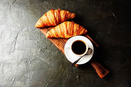 The concept of a delicious breakfast, croissants and espresso on a dark wooden board, on gray concrete, view from the top, flat lay Standard-Bild - 138720837