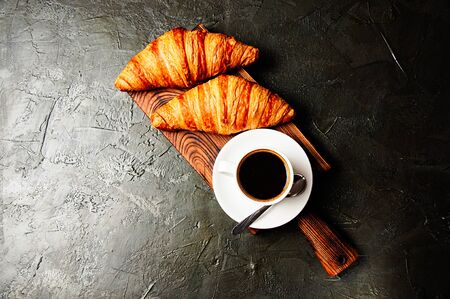The concept of a delicious breakfast, croissants and espresso on a dark wooden board, on gray concrete, view from the top, flat lay Standard-Bild - 138720594