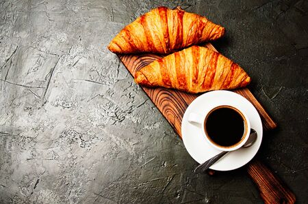 The concept of a delicious breakfast, croissants and espresso on a dark wooden board, on gray concrete, view from the top, flat lay Standard-Bild - 138720895