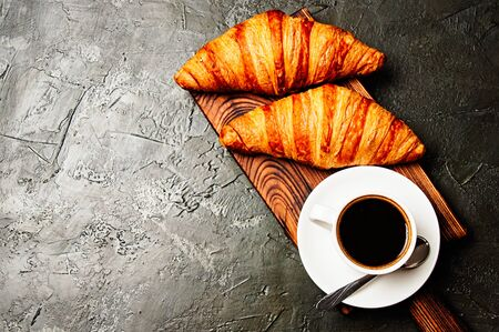 The concept of a delicious breakfast, croissants and espresso on a dark wooden board, on gray concrete, view from the top, flat lay Standard-Bild - 138720822