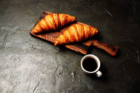 Tasty croissants and coffee in a white cup on a dark background Standard-Bild - 138720959