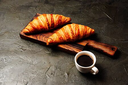 Tasty croissants and coffee in a white cup on a dark background Standard-Bild - 138726992