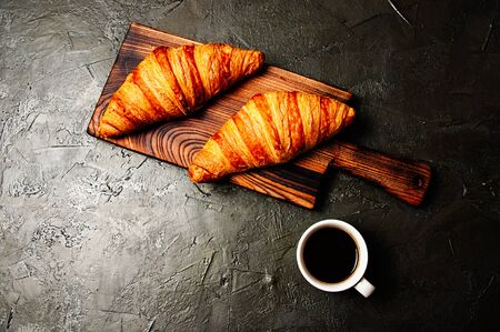 Tasty croissants and coffee in a white cup on a dark background, flat lay Standard-Bild - 138726993