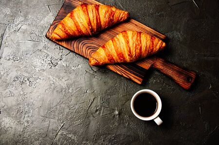 Tasty croissants and coffee in a white cup on a dark background, flat lay Standard-Bild - 138720941