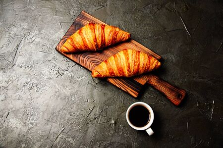 Tasty croissants and coffee in a white cup on a dark background, flat lay Standard-Bild - 138720863