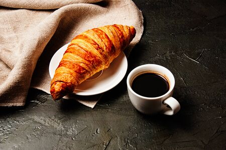 Sweet croissant on a saucer, a cup of ristretto coffee and a linen towel on a dark background Standard-Bild - 138720898