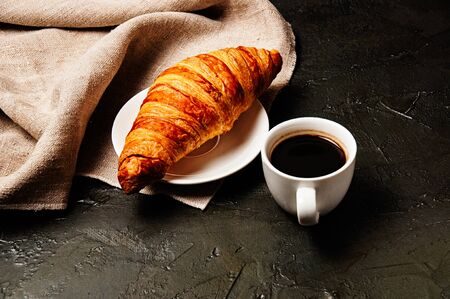Sweet croissant on a saucer, a cup of ristretto coffee and a linen towel on a dark background Standard-Bild - 138720752