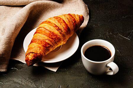 Croissant dolce su un piattino, una tazza di caffè ristretto e un asciugamano di lino su uno sfondo scuro Archivio Fotografico