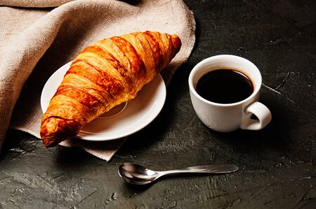 Sweet croissant on a saucer, a cup of strong ristretto coffee, a spoon and a linen towel on a dark background Standard-Bild - 138720794