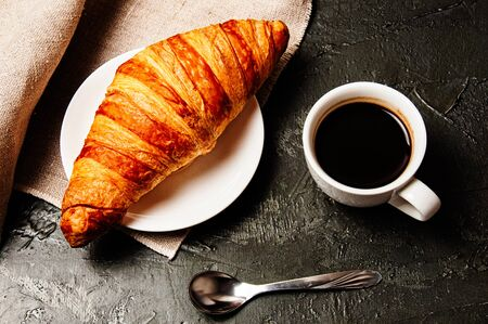 Sweet croissant on a saucer, a cup of strong ristretto coffee, a spoon and a linen towel on a dark background Standard-Bild - 138720790