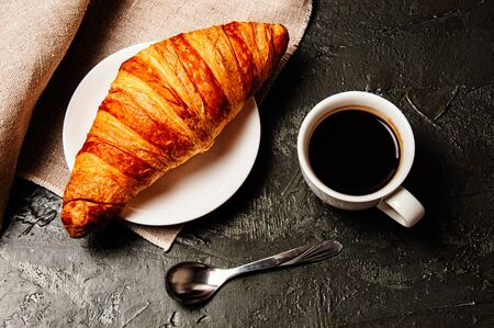 Sweet croissant on a saucer, a cup of strong ristretto coffee, a spoon and a linen towel on a dark background Standard-Bild - 138720551