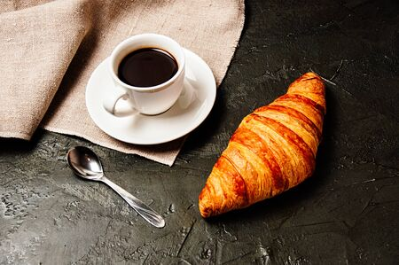 Sweet tasty croissant, a cup of strong ristretto coffee on a saucer, a spoon and a linen towel on a dark background Standard-Bild - 138720809