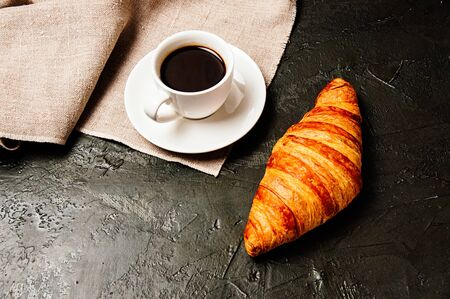 Tasty rustic breakfast. Croissant and coffee in a white cup, top view, flat lay Standard-Bild - 138720927
