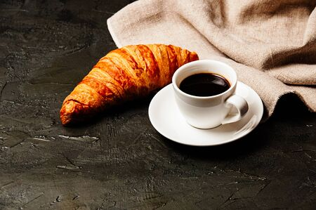 Sweet tasty croissant, a white cup of strong ristretto coffee on a saucer and a linen towel on a dark background with copy space Standard-Bild - 138720954