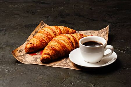 Sweet tasty croissants, a white cup of strong ristretto coffee on a saucer on craft paper on a dark background with copy space