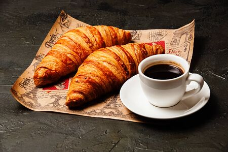 Sweet tasty croissants, a white cup of strong ristretto coffee on a saucer on craft paper on a dark background with copy space Standard-Bild - 138720845