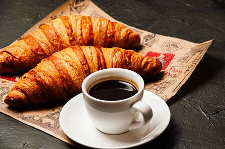 Sweet tasty croissants, a white cup of strong ristretto coffee on a saucer on craft paper on a dark background with copy space Standard-Bild - 138720964