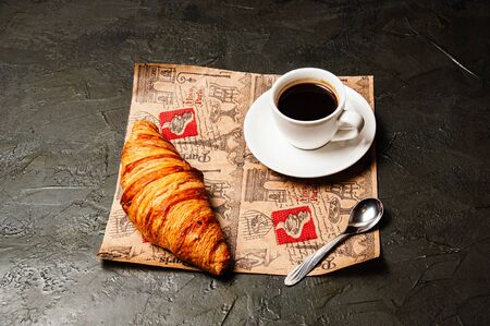 French croissant, sweet strong coffee in a white cup on a saucer with a spoon, on a beautiful craft paper, on a dark background Standard-Bild - 138720973