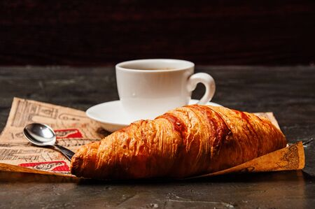 French croissant, sweet strong coffee in a white cup on a saucer with a spoon, on a beautiful craft paper, on a dark background Standard-Bild - 138720797