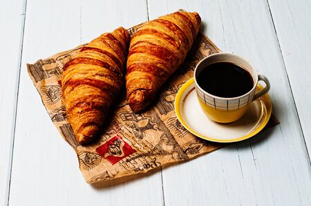 Espresso coffee in a vintage yellow cup and saucer, croissants on craft paper, on a light background, breakfast concept Standard-Bild - 138721034