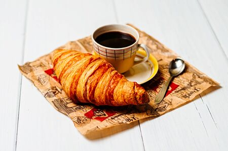 Espresso coffee in a vintage yellow cup with a saucer and spoon, croissants on craft paper, on a light background, breakfast concept Standard-Bild - 138721072