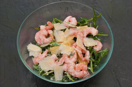 Salad with shrimp, arugula and cheese in a glass bowl or plate, fork dark background Imagens