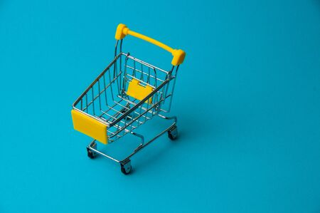 Trolley for shopping on blue background. Supermarket food price concept, holiday discounts Stock Photo