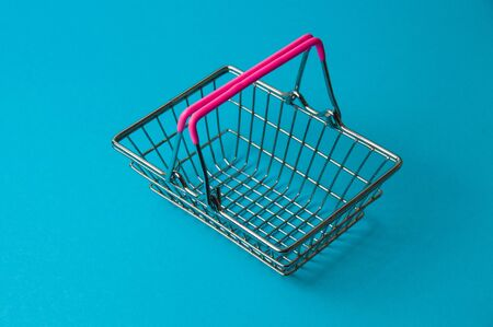 Shopping basket on blue background. Supermarket food price concept, holiday discounts