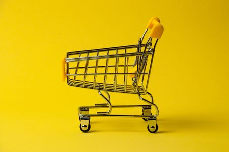 Cart for shopping on yellow background. Supermarket food price concept, holiday discounts