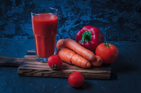 Juice and vegetables, tomato, carrots and peppers on wooden board. Still life in dark colors Stock Photo