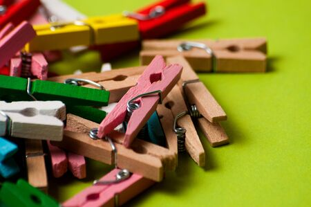 Multicolored decorative wooden clothespins on green background, macro closeup, copy space 版權商用圖片