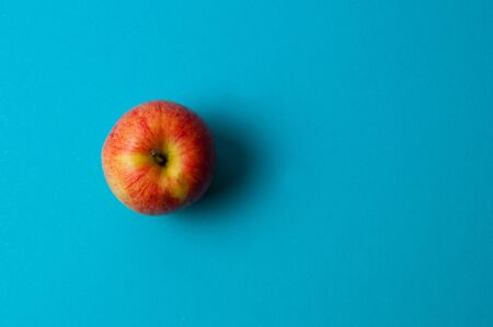 Apple on blue background. Healthy eating, calorie count and weight loss concept 免版税图像