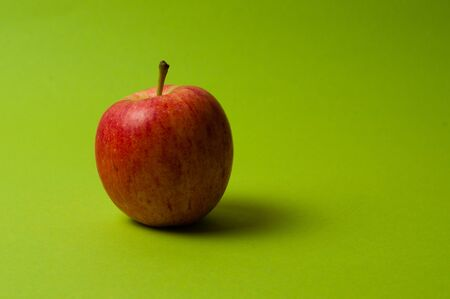 Apple on a green background. Healthy eating, calorie count and weight loss concept
