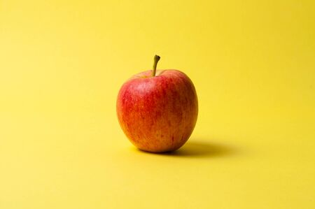 One red apple on yellow background. The concept of ideas, weight loss and proper nutrition