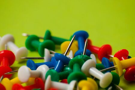 Many thumbtacks of different colors on green designer paper.