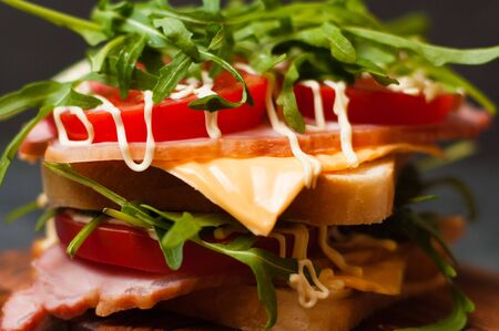 Very appetizing tasty big sandwich with ham or balyk, arugula, cheese, tomatoes and mayonnaise on a cutting board in rustic style on a gray background view from side close-up, copy space