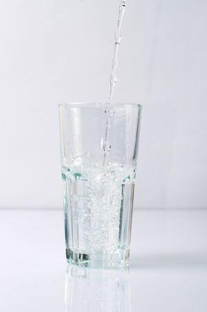 Splashing liquid water is pouring into a glass Standard-Bild