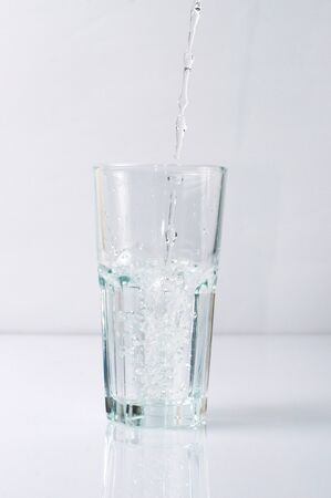Splashing liquid water is pouring into a glass Reklamní fotografie