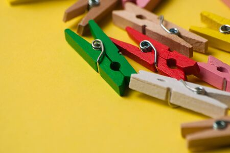 Multicolored decorative wooden clothespins on yellow ocher background, macro closeup, copy space
