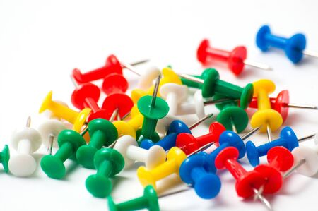 Multicolored push pins on a white background close-up