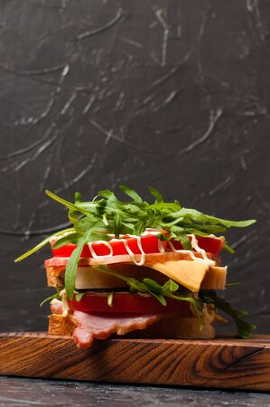 Very appetizing tasty large sandwich with ham or balyk, arugula, cheese, tomatoes and mayonnaise on a cutting board in a rustic style on gray background view from the side, copy space