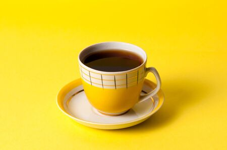 Yellow cup of tea or coffee on a yellow background. Minimalistic composition with avintage subject and place for text.